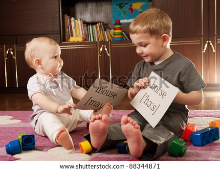 A boy aged three and a girl aged one are playing with blocks and cards with words - stock photo