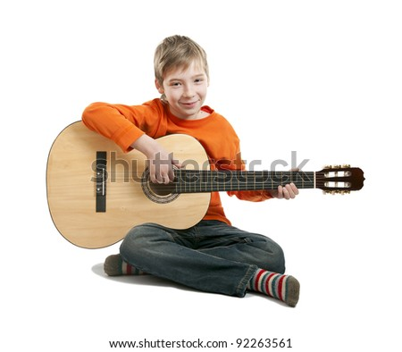 A boy aged 11 years learning to play guitar - stock photo