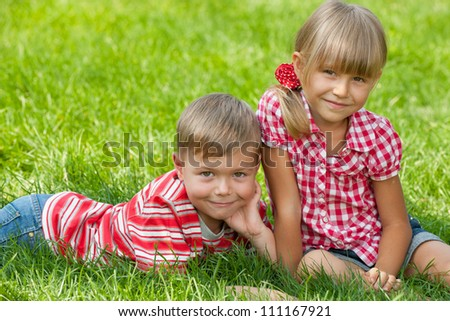 A boy and a girl are resting on the green grass in summer - stock photo