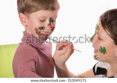 a boy and a girl having fun painting face painting