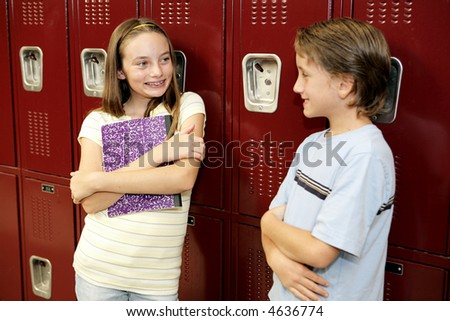 A boy and a girl in school, chatting by their lockers. - stock photo