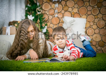 a boy and a girl reading a book lying on the carpet, brother and sister at home, leisure winter evening - stock photo