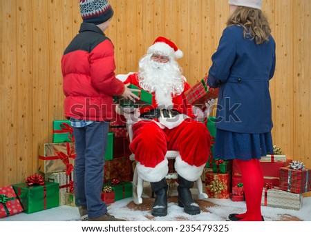 A boy and a girl receiving Christmas gifts from Santa in his grotto - stock photo