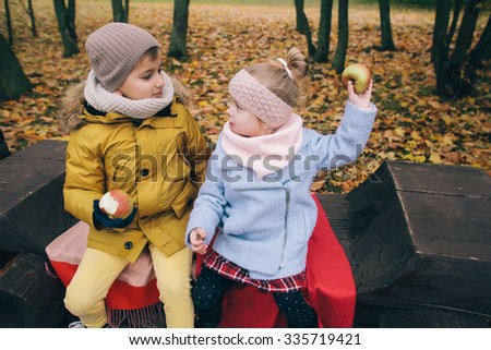 a boy and a girl sitting on a bench in the park - stock photo
