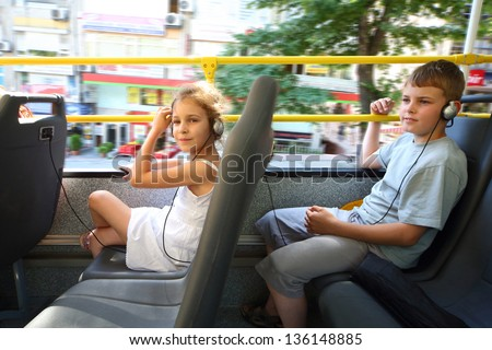 A boy and a girl traveling in a tour bus with headphones - stock photo