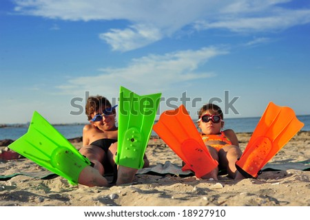 A boy and a girl with flippers standing on beach - stock photo