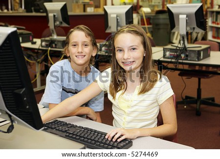A boy and girl doing research in the school computer lab. - stock photo