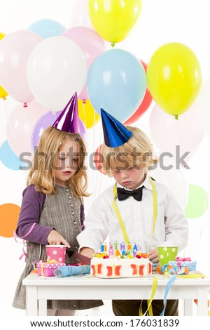 A boy and girl looking at a birthday cake and many balloons over their heads.