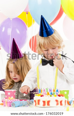 A boy and girl wearing party hats while the boy licks his fingers.