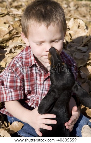 A boy and his dog playig in the leaves outdoors.