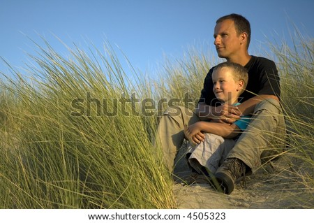 A boy and his father are looking far away, to the horizon. They are sitting in the dunes.