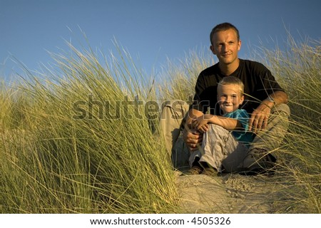 A boy and his father are looking far away, to the horizon. They are sitting in the dunes. - stock photo