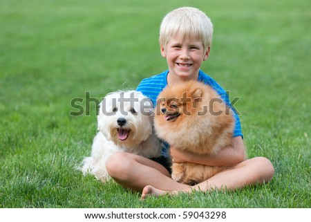 A boy and his pets are sitting on the green grass