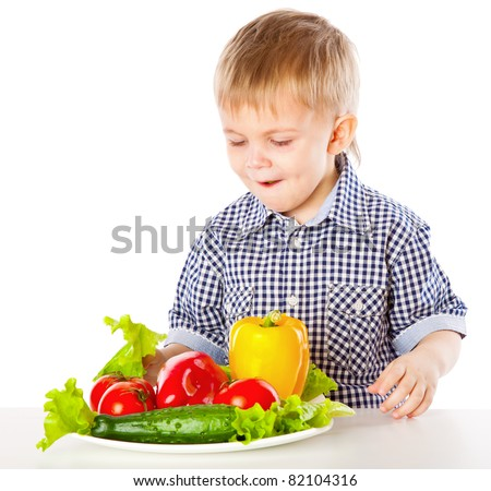 A boy and the plate of vegetables. Isolated on a white background - stock photo