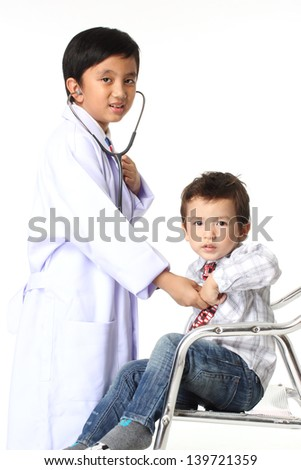 A Boy as doctor are listening a little boy - stock photo