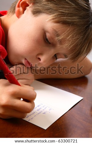 A boy at a table writing his wishlist for Santa for Christmas. - stock photo