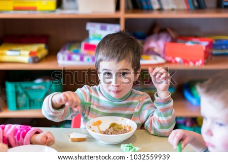 A boy at the age of 5 years eating soup in the kindergarten.
