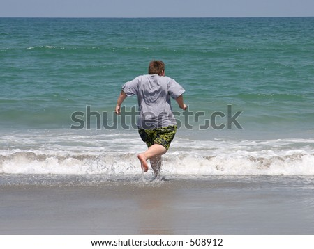 a boy at the beach, running to swim in the ocean - stock photo