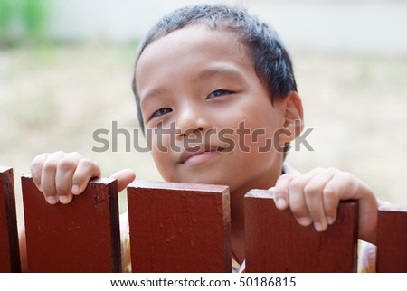 A boy  behind the fence - stock photo
