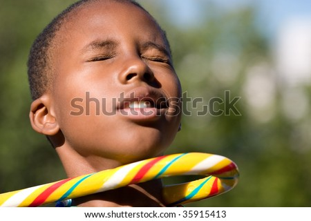 a boy being hooked by a giant candy cane - stock photo