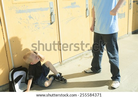 A boy bullying another in school playground - stock photo