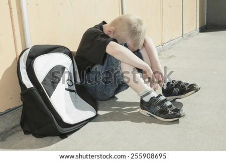 A boy bullying in school playground. very sad! - stock photo