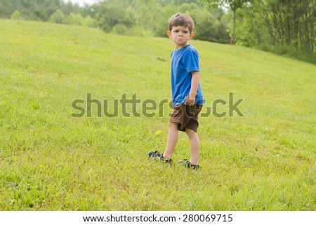 A boy climbing a hill outside in a park setting. He is making a sad, disappointed face.  - stock photo