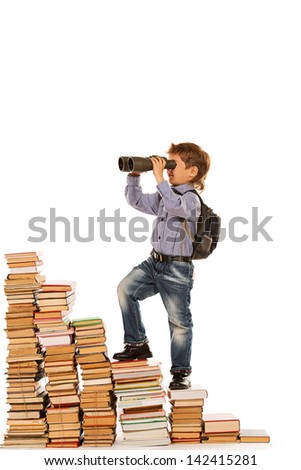 A boy climbing the stairs of books and looking into the distance through binoculars. Isolated over white. - stock photo