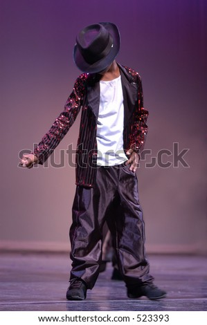 A boy dances on the stage imitating Micheal Jackson. - stock photo