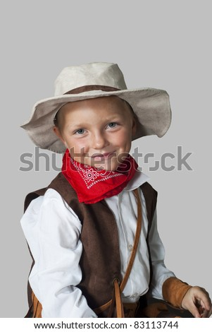 A boy dressed as a cowboy on a gray background