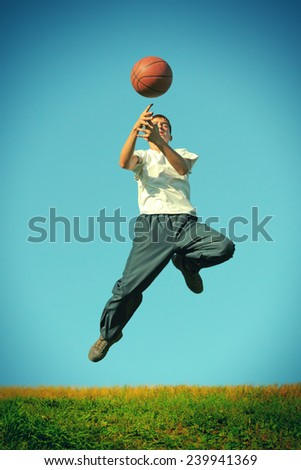 a boy dribbling a basketball in a game - stock photo