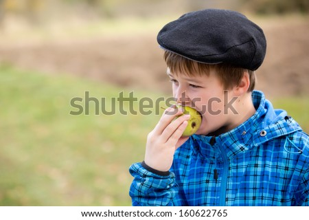 A boy eating a fresh pear - stock photo