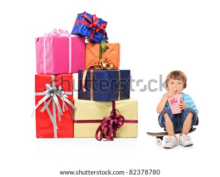 A boy eating a popcorn and pile of gifts isolated on white background - stock photo