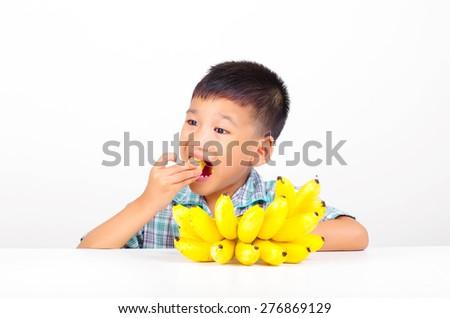 a boy eating banana fruit - stock photo