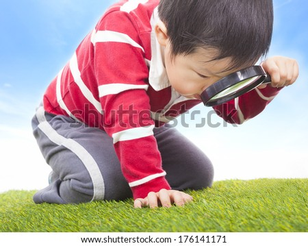 a boy exploring nature with magnifying glass - stock photo