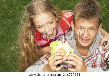 A boy feeding a girl a burger. - stock photo