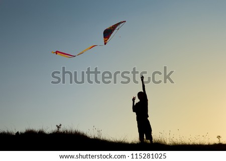 A boy flies a kite in the sky at sunset - stock photo