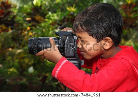 A boy focusing with a camera fixed on tripod - stock photo