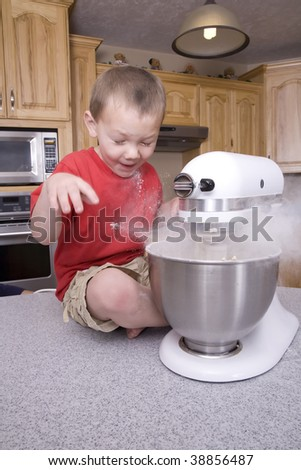 A boy getting a surprise by the flour flying out of the mixture.