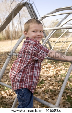 A boy getting ready to climb the equipment at the park. - stock photo