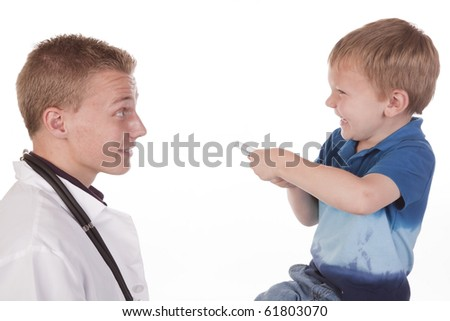 A boy getting to shine a light into his doctors eyes for fun. - stock photo
