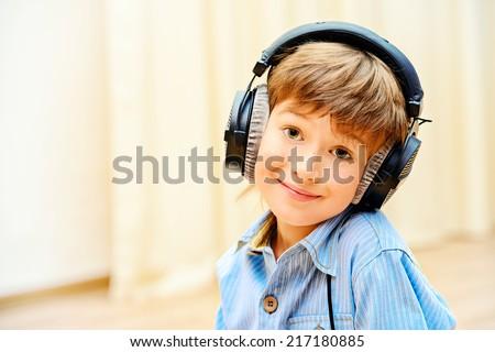 A boy having fun listening to music on headphones. - stock photo