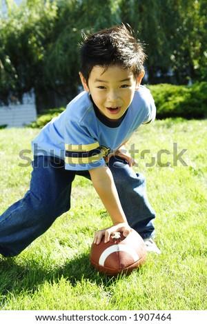 A boy having fun playing football - stock photo