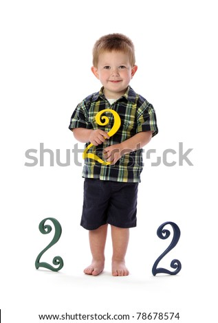 A boy hods a number two to represent his turning two years old - stock photo
