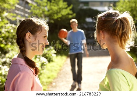 A boy holding a basketball walking towards two girls. - stock photo