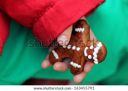 A boy holds a Gingerbread cookie man in his hand - stock photo