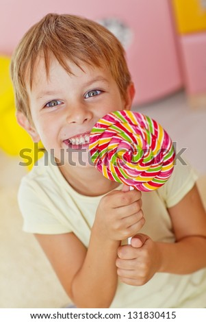 A boy holds a large colorful lollipop - stock photo