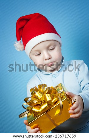 A boy in a cap of Santa Claus with gifts on a blue background - stock photo