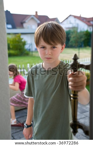 A boy in a green t-shirt stands in an open door with an angry, troubled expression on his face. His sister appears in the background.  The brother and sister have been arguing, and he is angry. - stock photo