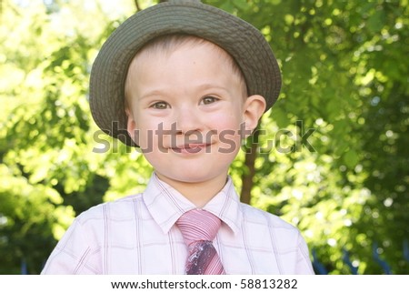 A boy in a hat and tie looks straight ahead